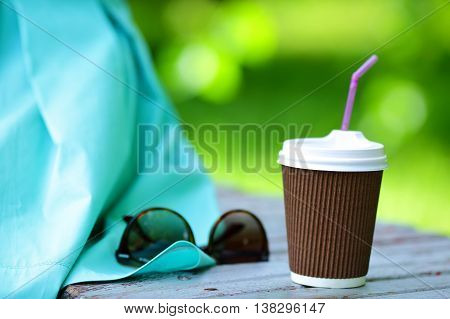 Disposable Coffee cup and Sunglasses on summer outdoors