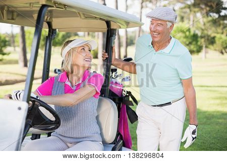 Smiling golfer woman looking at man while sitting in golf buggy