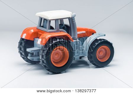 Small red toy tractor on light background, shallow depth of field
