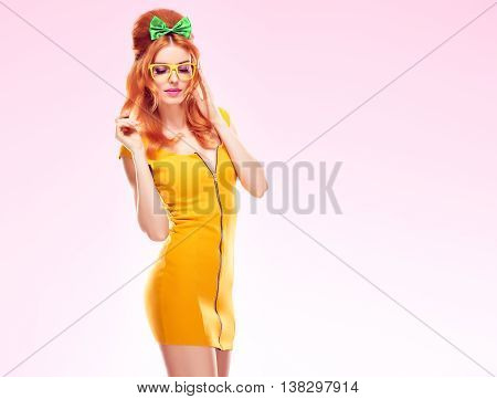 Fashion woman in Summer dress, Pinup hairstyle, Trendy fashion Glasses. Beauty sexy Redhead Model, Glamor Outfit, Stylish Fashion doll.Playful model Pinup fashion girl on pink.Unusual creative fashion
