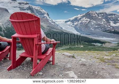 Behind View of Woman Sitting In Chair Enjoying the View in the Canadian Rockies