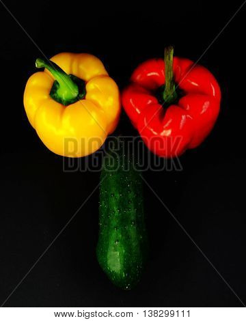 composition of the freakish form on a black background two peppers and cucumber