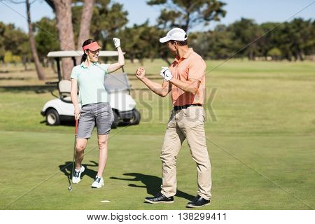 Smart golfer couple celebrating success while standing on field