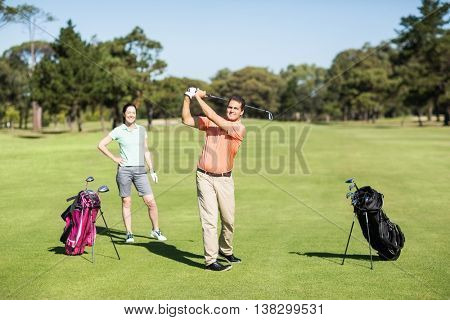 Happy golfer taking shot while standing by woman