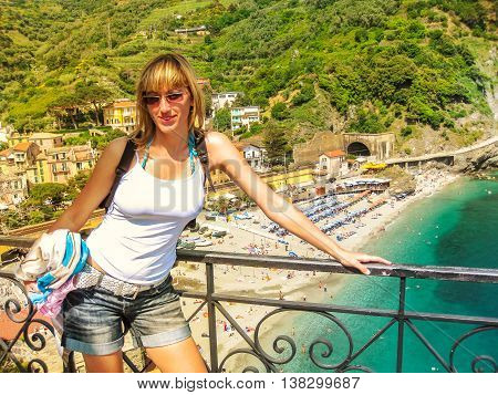 Young woman tourist posing with behind the panoramic view of Monterosso al Mare Beach. Cinque Terre National Park, Italy.