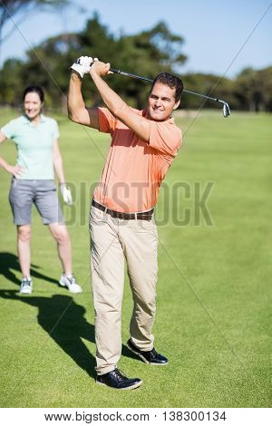 Cheerful golfer taking shot while standing by woman