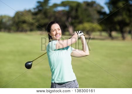 Cheerful woman taking shot while standing at golf course