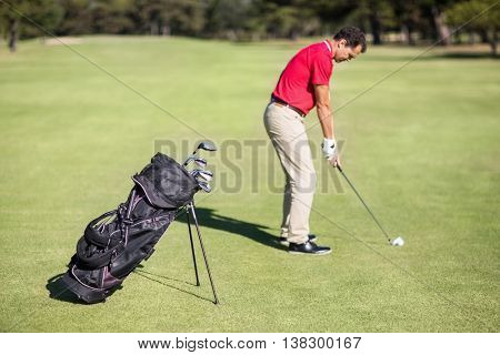 Full length side view of man playing golf while standing on field