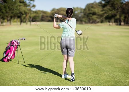 Full length rear view of golfer woman taking shot while standing at golf course