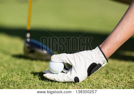 Cropped image of woman holding golf ball while crouching on field