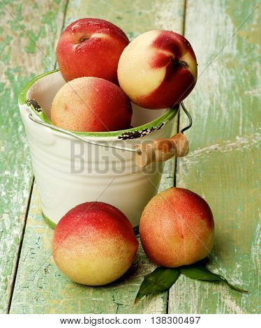 Heap of Perfect Ripe Small Nectarines in White Garden Bucket closeup on Cracked Wooden background
