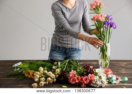 Girl in gray blouse and jeans make bouquet over gray background, putting alstroemerias and irises in vase, flowers and vase on wood table.