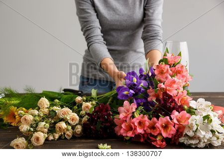 Girl in gray blouse and jeans make bouquet over gray background, hanging alstroemerias and irises in hands, flowers and vase on wood table.