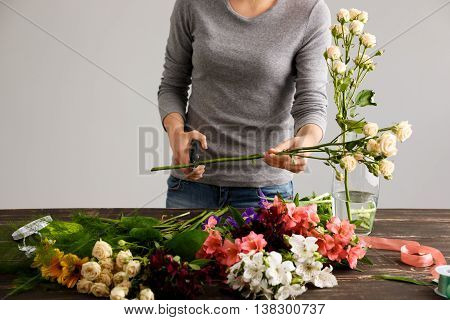 Girl in gray blouse and jeans make bouquet over gray background, cutting rose stem, flowers and vase on wood table.