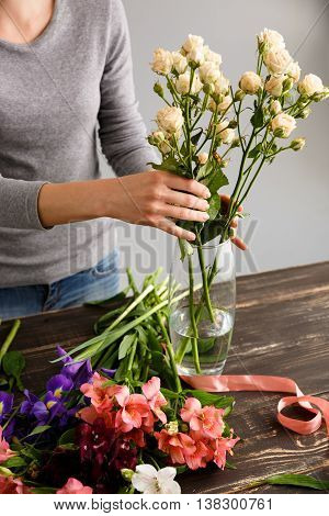 Girl  in gray blouse and jeans make a bouquet over gray background, putting roses in vase, flowers, ribbon and vase on wood table.