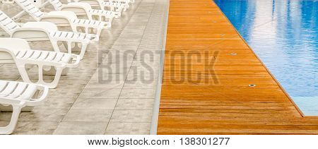 clean swimming pool and empty resting chairs