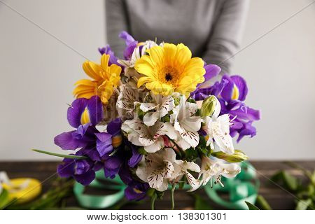 Girl in gray blouse and jeans make bouquet of herberas, irises and alstroemerias over gray background. Focus on bouquet.
