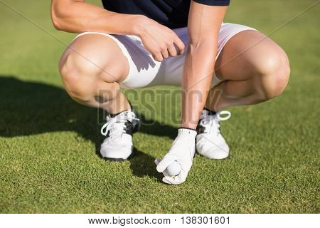 Low section of man placing golf ball on tee while crouching on field
