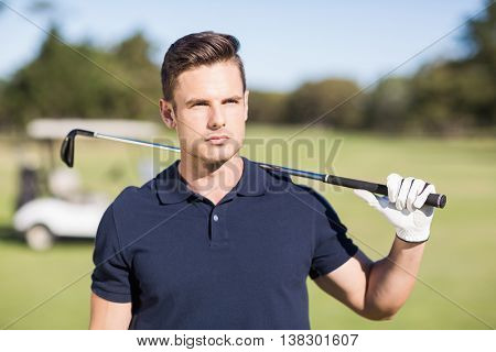 Confident young man carrying golf club while standing on field