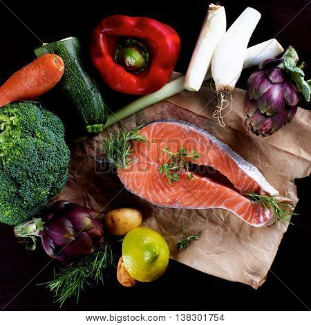 Raw Steak of Salmon and Heap of Raw Vegetables with Broccoli Artichokes Spring Onion Potato Red Bell Pepper and Lemon closeup on Parchment Paper. Top View on Dark Wooden background