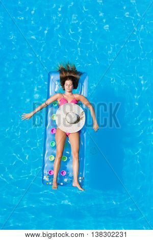 Relaxing in a swimming pool on an air mattress