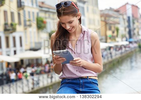 Young female tourist is searching way in navigation on touch pad, while resting after tour in old church. Woman is enjoying good movie on digital tablet during her free time in weekend