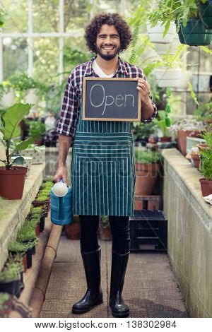 Portrait of happy male gardener holding open sign placard and watering can at greenhouse