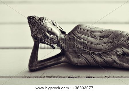 closeup of a representation of the buddha laying down, on a pale green rustic background