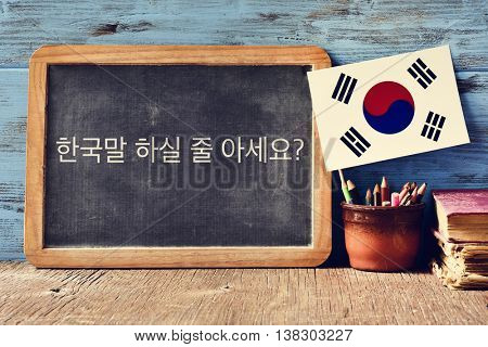 a chalkboard with the question do you speak Korean? written in Korean, a pot with pencils, some books and the flag of South Korea, on a wooden desk