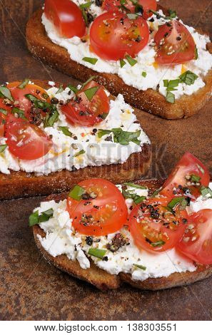 Bruschetta with ricotta and cherry tomatoes seasoned spices basil