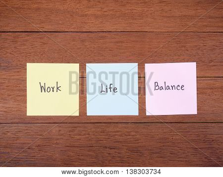 Word spell Work Life Balance on dark wood background in top view