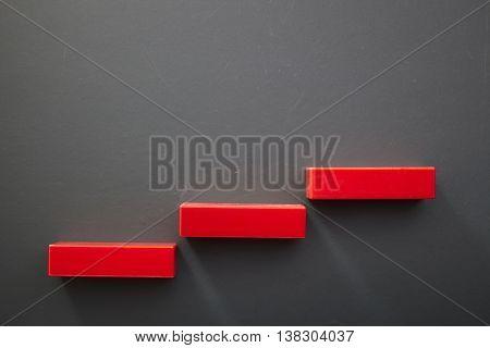 plastic blocks form a stair on blackboard