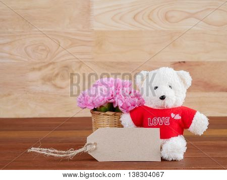 Brown blank label teddy bear and bouquet pink Carnation flower on wood background (Love Concept)