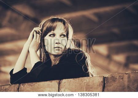Blonde woman recline on brick wall