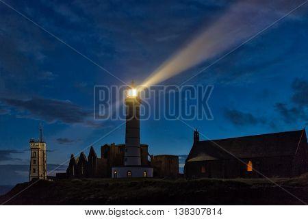 Mystical church and lighthouse illuminated over cloudy sky at Saint Mathieu point, Brittany, France