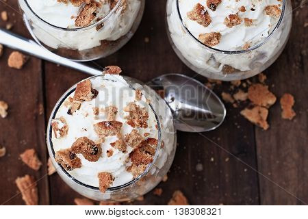 Three glasses of crumbled chocolate chip cookies and cheesecake parfaits against a rustic background. Extreme shallow depth of field with selective focus on top of desserts.