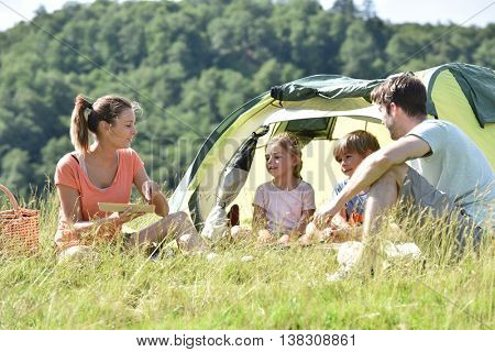 Family of four in camp tent
