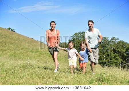 Family on vacation running down the hill