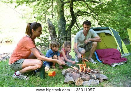 Family camping and cooking sausages in campfire