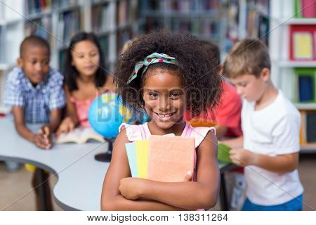 Portrait of happy girl holding books against classmates in library