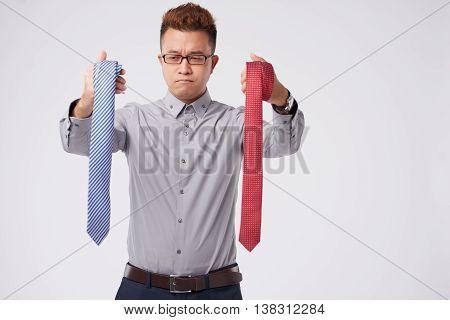 Vietnamese man choosing between two different ties