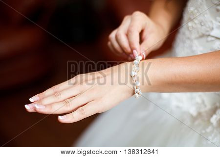 Bride wrapping pearl bracelet on hand closeup