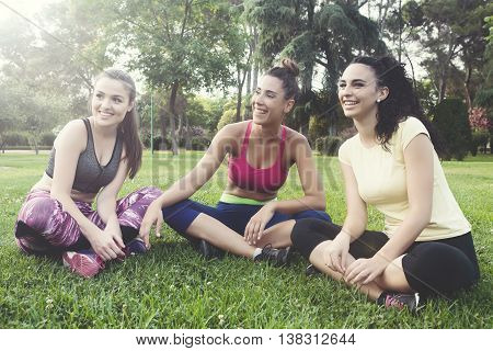 Portrait of cheerful candid athletes laughing while sitting on grass