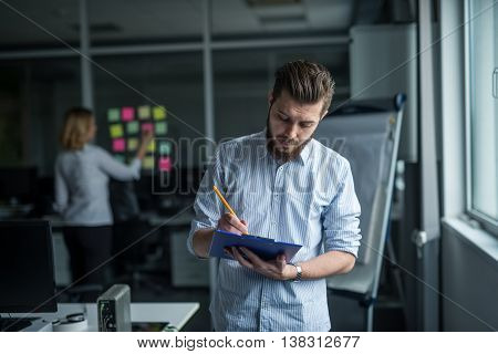 Handsome businessman taking notes in an office.
