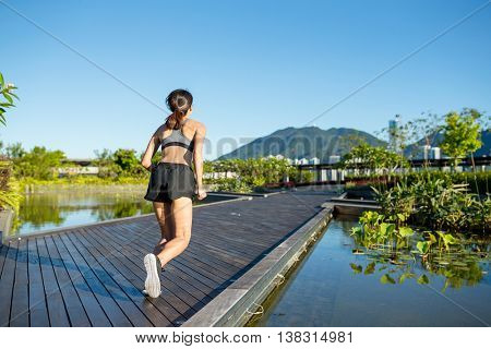 Woman running in a boardwalk
