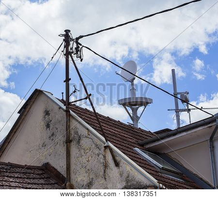 Telecommunication antenna on a roof with electric cables.