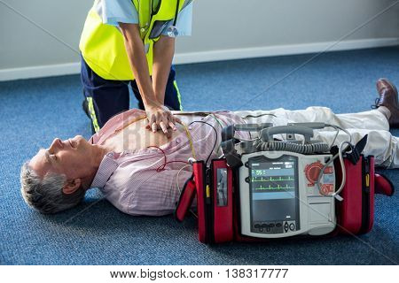 Paramedic using an external defibrillator during cardiopulmonary resuscitation in hospital