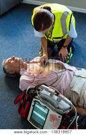 Paramedic examining a patient during cardiopulmonary resuscitation in hospital