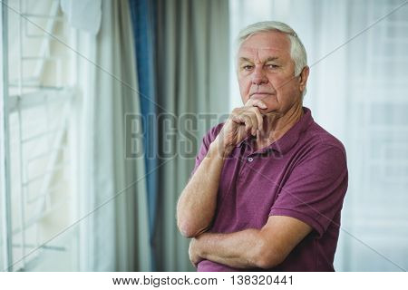 Portrait of thoughtful senior man standing with hand on chin