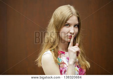 Young beautiful blonde woman has put forefinger to lips as sign of silence, against wood wall